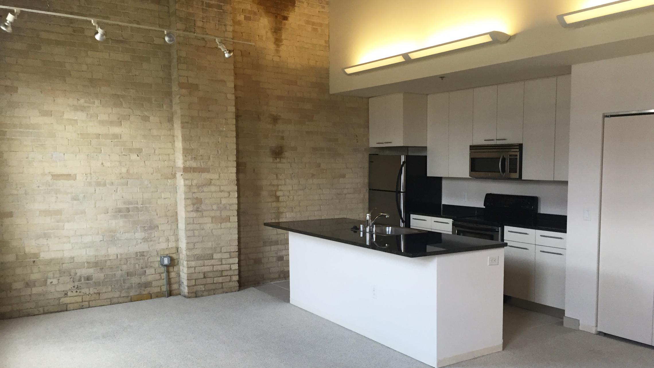 ULI Tobacco Lofts - E309 - Kitchen with Exposed Brick